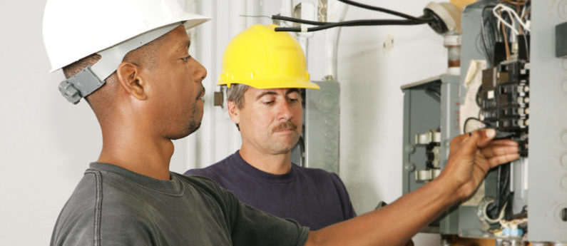 Two HVAC technicians in hard hats work on a panel.