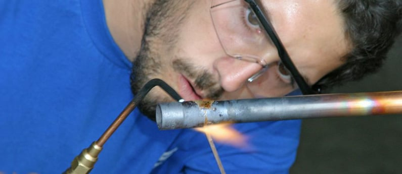 A Brownson student welding a pipe