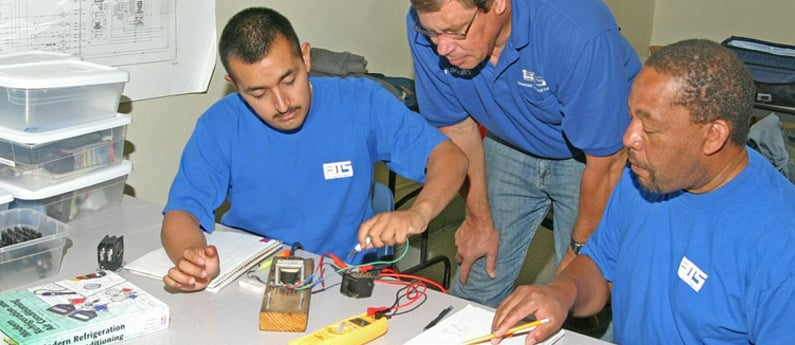 An instructor helps two HVAC students with an assignment