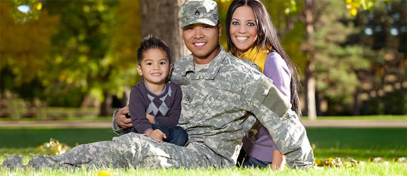 A smiling Military Family of 3, sitting on the grass in a park