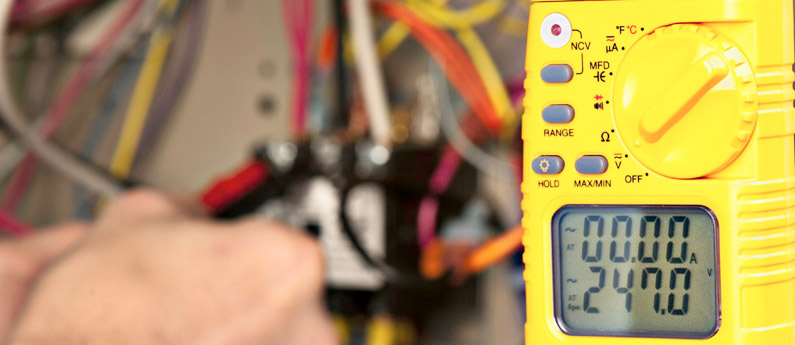An HVAC technician's device measures various readings while they work on the device in the background.