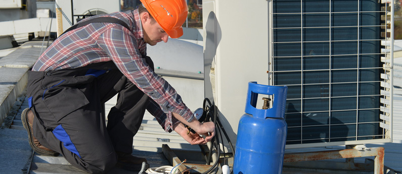 An HVAC technician works on an air conditioning unit